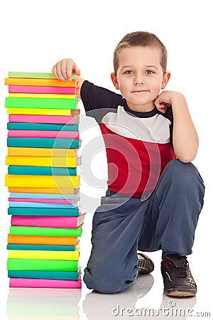 Élève du cours préparatoire et grands livres de pile