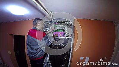 Électricien Trimming Electrical Wires avant la réparation à un BreakerPanel électrique banque de vidéos