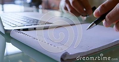 Équipez l'écriture sur le bloc-notes tout en à l'aide de l'ordinateur portable à la maison 4k banque de vidéos