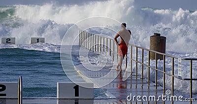Équipez la position observant de grandes vagues frapper des bains d'océan banque de vidéos