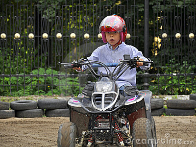 Équitation de garçon sur le quadricycle des gosses, ayant l amusement