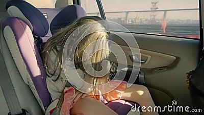 Équitation mignonne de petite fille dans la voiture au siège arrière et au sommeil Fille adorable clips vidéos