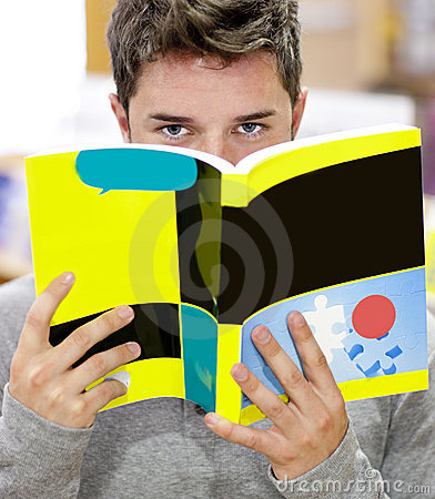 Étudiant mâle cachant son visage derrière un livre
