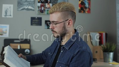 Étudiant mûr occasionnel d'homme de hispter avec les cheveux jaunes de coupe de cheveux élégante reposant à la maison le bureau l banque de vidéos