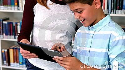 Étudiants heureux à l'aide du comprimé numérique dans la bibliothèque clips vidéos
