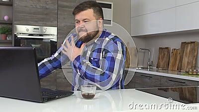 Άτομο με μια γενειάδα που λειτουργεί σε ένα lap-top σε μια σύγχρονη εγχώρια κουζίνα, απογοήτευση, θυμός, σε αργή κίνηση απόθεμα βίντεο