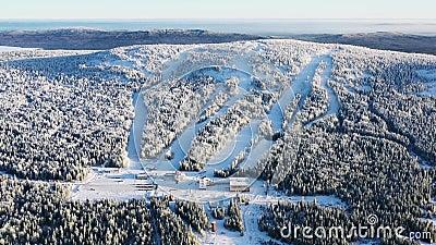 Άποψη της σύγχρονων βάσης σκι και των διαδρομών σκι που περιβάλλονται από το δάσος το χειμώνα ενάντια στο μπλε ουρανό footage ενα απόθεμα βίντεο