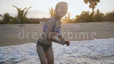 Ειδυλλιακός πυροβολισμός κινηματογραφήσεων σε πρώτο πλάνο ευτυχής λίγου 5-7χρονου καυκάσιου κοριτσιού που παίζει στα ωκεάνια κύμα απόθεμα βίντεο
