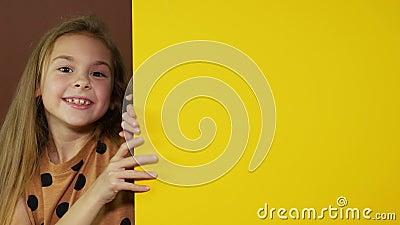 Εύθυμο κορίτσι που δείχνει στο κενό διάστημα για το κείμενο Κίτρινο υπόβαθρο για τη διαφήμιση φιλμ μικρού μήκους