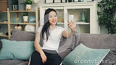 Ευτυχής ασιατική νέα κυρία στην παραγωγή της σε απευθείας σύνδεση τηλεοπτικής κλήσης που χρησιμοποιεί το σύγχρονο smartphone που  απόθεμα βίντεο