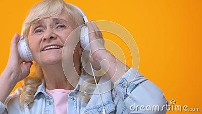 Ηλικιωμένη γυναίκα στα άσπρα ακουστικά που ακούει τη μουσική, που απολαμβάνει την αγαπημένη μελωδία φιλμ μικρού μήκους