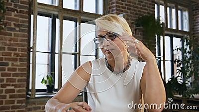 Η ελκυστική πολυάσχολη γυναίκα στα γυαλιά καταγράφει κάτι στη συνεδρίαση ημερολογίων πίσω από το γραφείο στο γραφείο indoors Επιχ απόθεμα βίντεο