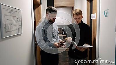 Οι άνδρες συνάδελφοι συζητούν τα ζητήματα εργασίας που πηγαίνουν στο διάδρομο του κτιρίου γραφείων απόθεμα βίντεο