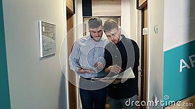 Οι άνδρες συνάδελφοι συζητούν τα ζητήματα εργασίας που πηγαίνουν στο διάδρομο του κτιρίου γραφείων φιλμ μικρού μήκους