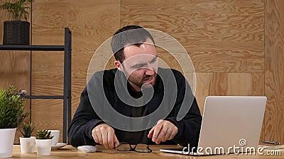 Ο ματαιωμένος επιχειρηματίας που κρατά το κεφάλι του κάθεται στο γραφείο απόθεμα βίντεο