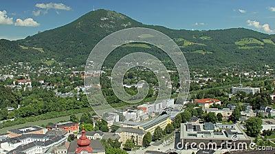 Σύγχρονη περιοχή της μικρής ευρωπαϊκής πόλης στη βάση του γραφικού λόφου με το πυκνό δάσος στις κλίσεις φιλμ μικρού μήκους