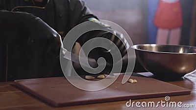 Συντριβή αρχιμαγείρων με το αιχμηρό αρωματικό σκόρδο μαχαιριών μετάλλων στον ξύλινο πίνακα για να προετοιμάσει το μαρινάρισμα στο φιλμ μικρού μήκους