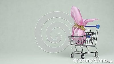 Το ανθρώπινο χέρι γεννά ένα ρόδινο αυγό Πάσχας δώρων σε ένα άσπρο υπόβαθρο καλαθιών αγορών, διάστημα αντιγράφων, υπεραγορά έννοια απόθεμα βίντεο