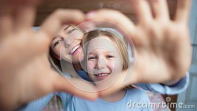 Το πορτρέτο κινηματογραφήσεων σε πρώτο πλάνο της ευτυχούς μητέρας και η κόρη που παρουσιάζει χειρονομία αγαπούν την καρδιά με το  φιλμ μικρού μήκους
