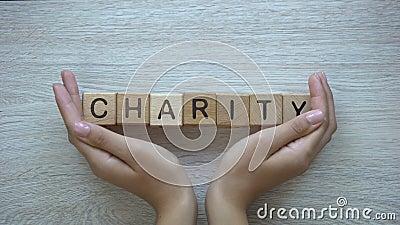 Φιλανθρωπία, χέρια που ωθούν τη λέξη στους ξύλινους κύβους, δωρεές και βοήθεια στην ανάγκη απόθεμα βίντεο