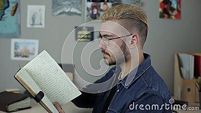 Περιστασιακός ώριμος σπουδαστής ατόμων hispter με το μοντέρνο γραφείο συνεδρίασης τρίχας κουρέματος κίτρινο στο σπίτι που διαβάζε απόθεμα βίντεο