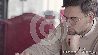 Πορτρέτο της όμορφης συνεδρίασης τύπων σε έναν καφέ, αναμονή για τη διαταγή του ή στην πλήμνη και εργασία με προσήλωση στον υπολο απόθεμα βίντεο