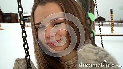 Πορτρέτο του εθνικού κοριτσιού με τη μακρυμάλλη ταλάντευση σε μια ταλάντευση Χιονώδης έκταση, καλό πρόσωπο χαμόγελου Στο υπόβαθρο φιλμ μικρού μήκους