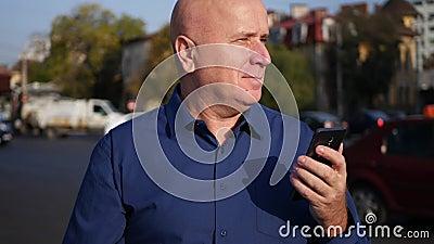 Бизнесмен идя на улицу в городском тексте используя соединение мобильного телефона видеоматериал