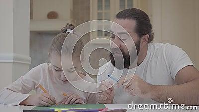 Бородатый человек смотря его чертеж маленькой девочки с отметками пока сидящ на таблице дома Советовать отца его акции видеоматериалы
