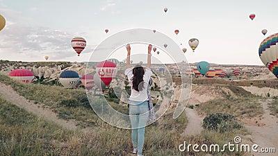 Восход солнца молодой женщины оставаясь на горе с баллонами горячего воздуха вокруг Устоичивая съемка кулачка сток-видео