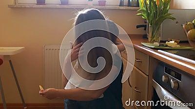 Женщина в кухне режет яблоки Ее маленькая дочь пришла бегущ Мама дает девушке часть яблока Здорово видеоматериал
