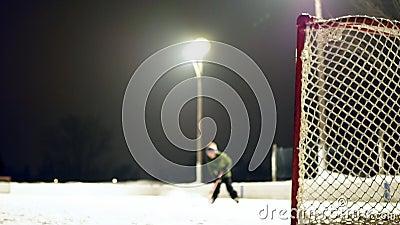 Запачканный зажим на открытом воздухе катка вечером с мальчиком катаясь на коньках и снимая шайбу видеоматериал