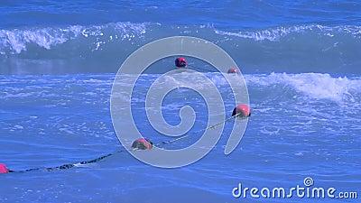 Красные заключая томбуи плавают на волны в море на лете акции видеоматериалы