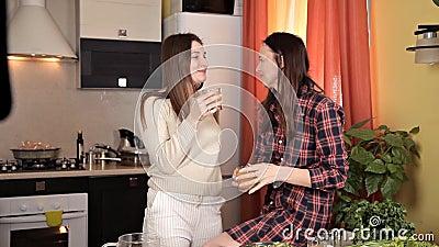 2 маленькой девочки беседуя в кухне пока варящ обедающий Община, друзья, еда акции видеоматериалы