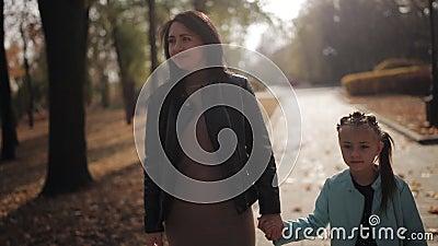 Мама и дочь идут вдоль бульвара посыпанного с листвой осени желтой Счастливая семья на прогулке в парке города видеоматериал