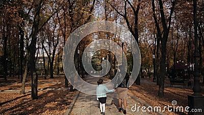 Мама и дочь идут вдоль бульвара посыпанного с листвой осени желтой Счастливая семья на прогулке в парке города акции видеоматериалы