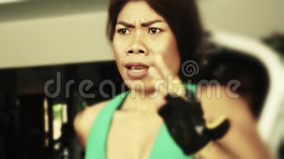 Молодая пригонка и атлетическая азиатская тайская женщина с подходящим телом бежать на разминке третбана спортзала потея тренируя видеоматериал