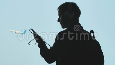 Молодой парень поворачивает на музыку на смартфоне и кладет дальше наушники на фоне самолета принимая  видеоматериал