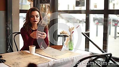 Модная дама в красном цвете используя мобильный телефон в кафе акции видеоматериалы
