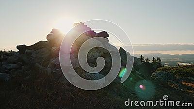 Небольшая насыпь камней лежит на верхней части горы Лучи блеска восходящего солнца из-за его традиционно видеоматериал