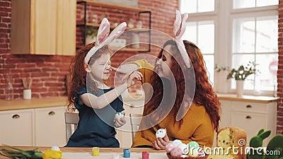 пасха счастливая Молодая мать и ее маленькая дочь покрасить друг друга яйца и стороны Шутки семьи акции видеоматериалы