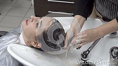 Парикмахер женщины мылит девушку главного шампуня восточную в салоне красоты Внимательность волос конец вверх 4K 25 fps акции видеоматериалы