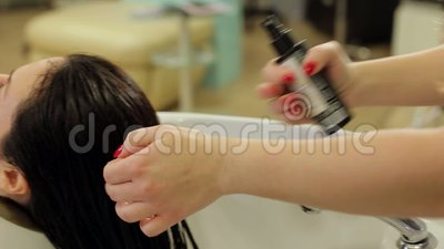 Парикмахер конца-вверх брызгает на масле влажной девушки волос защитном Внимательность волос видеоматериал