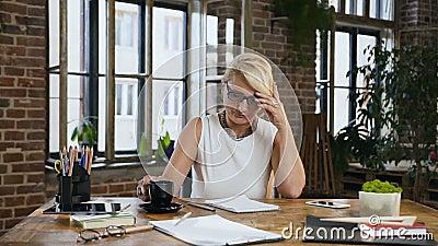 Привлекательная женщина проверяет отчетность в дневнике пока кофе напитков сидя за столом в домашнем офисе indoors видеоматериал