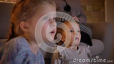 Портрет конца-вверх в профиле небольших кавказских девушек смотря фильм с большей занятностью в уютной домашней атмосфере сток-видео