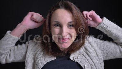 Портрет счастливой средн-достигшей возраста женщины брюнета кавказской показывая положительную занятность в камеру на черной пред сток-видео