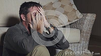 Драматическая съемка привлекательного грустного и подавленного человека сидя на поле живущей комнаты чувствуя отчаянная и усиленн