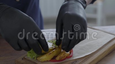 Шеф-повар в перчатках черной варки кладя свежие овощи, мясо барбекю и печеные картофели на хлеб питы на доске, сток-видео