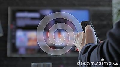 Человек держа дистанционное управление и ища для течь средства массовой информации для игры видеоматериал