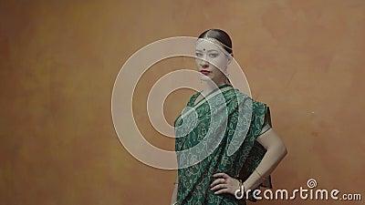 Решительная милая женщина в индусском сари представляя внутри помещения акции видеоматериалы